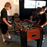 Boys playing foosball in game room