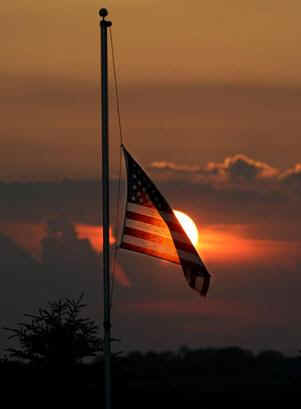 Flag at half staff at sunset