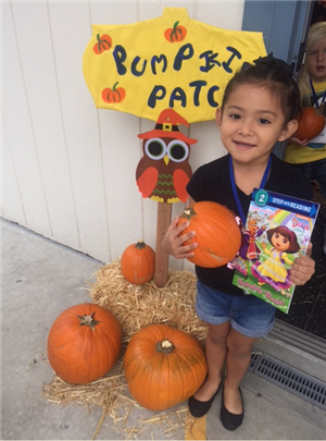 Pumpkin Patch at Oak View Preschool, little girl holding pumpkin.