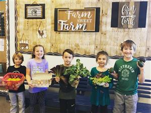 Golden View students with vegetables and sign Farm Sweet Farm